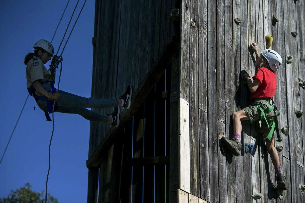 """Erin Heilbrun, 10, belays down as Katherine """"Kat"""" Nickels, 10, climbs up the climbing tower at McGimsey Scout Park during a training weekend for Scouts BSA, a new Scouts BSA program, which will launch in February 2019 featuring troops with all girls, on Dec. 1, 2018."""