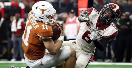 ARLINGTON, TEXAS - DECEMBER 01:  Sam Ehlinger #11 of the Texas Longhorns is tackled by Tre Brown #6 of the Oklahoma Sooners for a safety in the fourth quarter at AT&T Stadium on December 01, 2018 in Arlington, Texas. (Photo by Ronald Martinez/Getty Images)