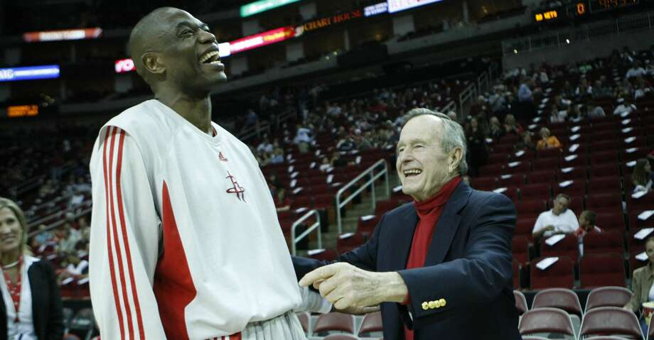 Houston Rockets center Dikembe Mutombo, left, laughs as he talks to President George Bush before his game against the Timberwolves Wednesday, March 26, 2008, in Toyota Center in Houston. ( Nick de la Torre / Chronicle ) Photo: Nick De La Torre/Houston Chronicle