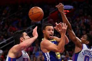 DETROIT, MICHIGAN - DECEMBER 01:  Stephen Curry #30 of the Golden State Warriors passes from between the defense of Langston Galloway #9 and Zaza Pachulia #27 of the Detroit Pistons during the first half at Little Caesars Arena on December 01, 2018 in Detroit, Michigan. NOTE TO USER: User expressly acknowledges and agrees that, by downloading and or using this photograph, User is consenting to the terms and conditions of the Getty Images License Agreement. (Photo by Gregory Shamus/Getty Images)