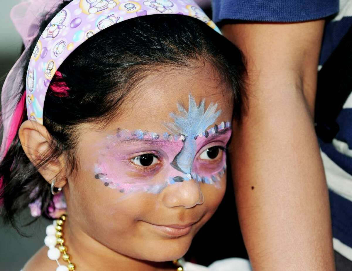 Mahesh Mattanmai, 6, of Guilderland stands in line for a pony ride with a design around her eyes she received when she had her face painted at GE Kids Day on Sunday, July 18, 2010, at the Empire State Plaza in Albany, NY. The General Electric sponsored event treated children to bouncy bounce setups, food, a petting zoo, pony rides, crafts, characters to meet and face painting for the day. Luanne M. Ferris / Times Union