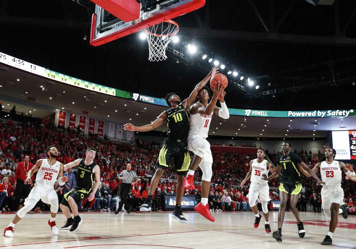UH guard Nate Hinton, right, takes the ball to the basket against Oregon's Victor Bailey Jr. before a capacity crowd at Saturday's unveiling of the Fertitta Center.