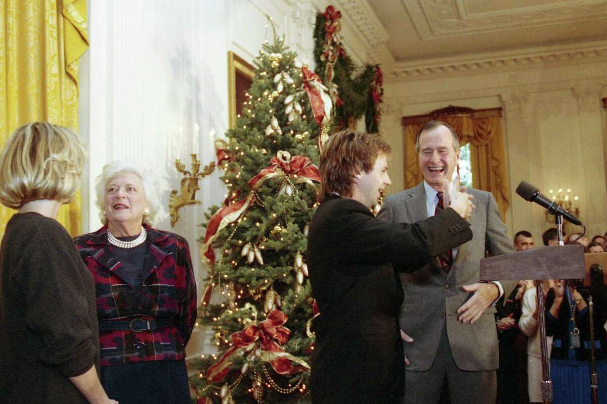 President George H.W. Bush cracks a smile as comedian Dana Carvey does his impersonation of Bush in December 1992.