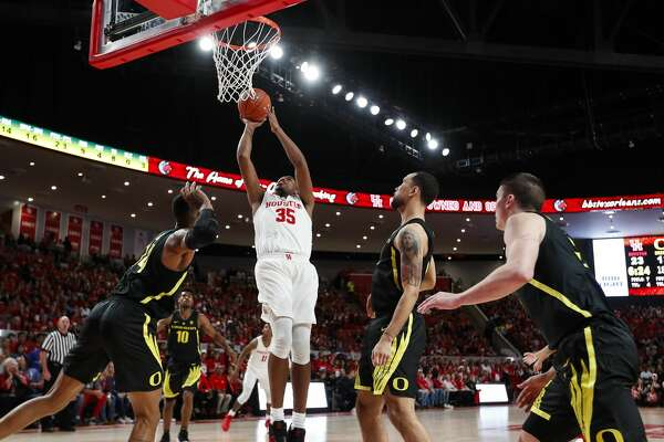 Houston forward Fabian White Jr. (35) takes a shot between a host of Oregon defenders during the first half on a NCAA basketball game at Fertitta Center on Saturday, Dec. 1, 2018, in Houston.
