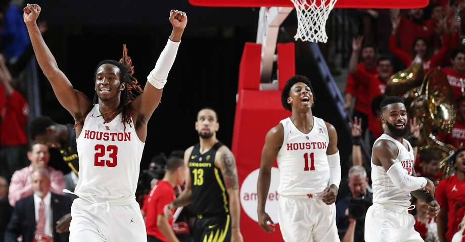 Houston forward Cedrick Alley Jr. (23), guard Nate Hinton (11) and guard Corey Davis Jr. (5) celebrate the Cougars' 65-61 win over Oregon during the second half on a NCAA basketball game at Fertitta Center on Saturday, Dec. 1, 2018, in Houston. Photo: Brett Coomer/Staff Photographer