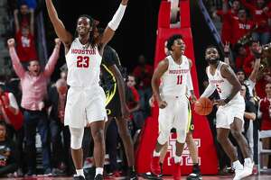 Houston forward Cedrick Alley Jr. (23), guard Nate Hinton (11) and guard Corey Davis Jr. (5) celebrate the Cougars' 65-61 win over Oregon during the second half on a NCAA basketball game at Fertitta Center on Saturday, Dec. 1, 2018, in Houston.
