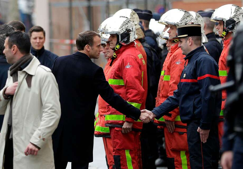 "French President Emmanuel Macron (L) shakes hands with a firefighter during a visit in the streets of Paris on December 2, 2018, a day after clashes during a protest of Yellow vests (Gilets jaunes) against rising oil prices and living costs. - Anti-government protesters torched dozens of cars and set fire to storefronts during daylong clashes with riot police across central Paris on December 1, as thousands took part in fresh ""yellow vest"" protests against high fuel taxes. (Photo by Geoffroy VAN DER HASSELT / AFP)GEOFFROY VAN DER HASSELT/AFP/Getty Images Photo: GEOFFROY VAN DER HASSELT;Geoffroy Van Der Hasselt / AFP / Getty Images"
