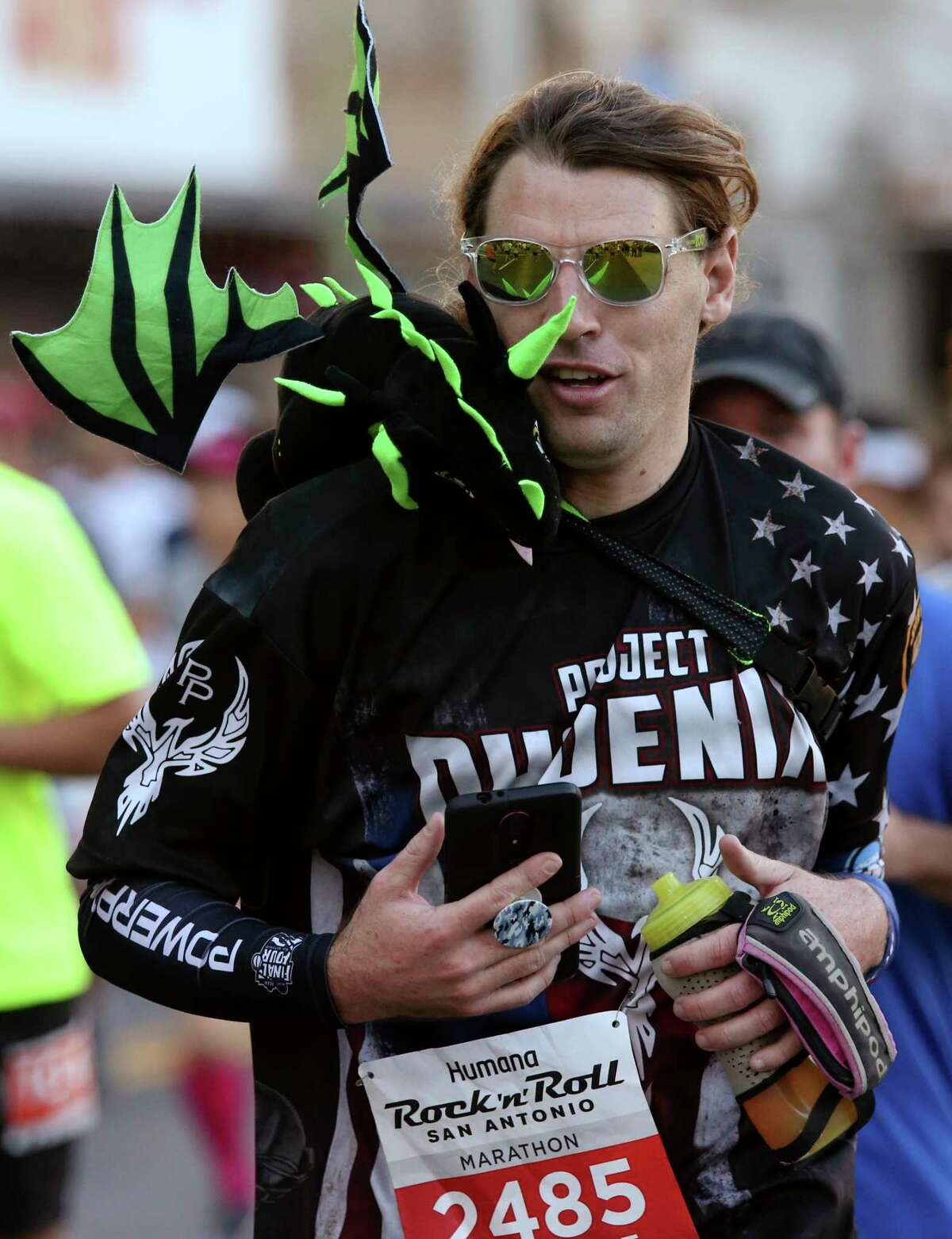Louis Johnson runs with a stuffed dragon during the 2018 Humana Rock 'n' Roll San Antonio Marathon and 1/2 Marathon, Sunday, Dec. 2, 2018.