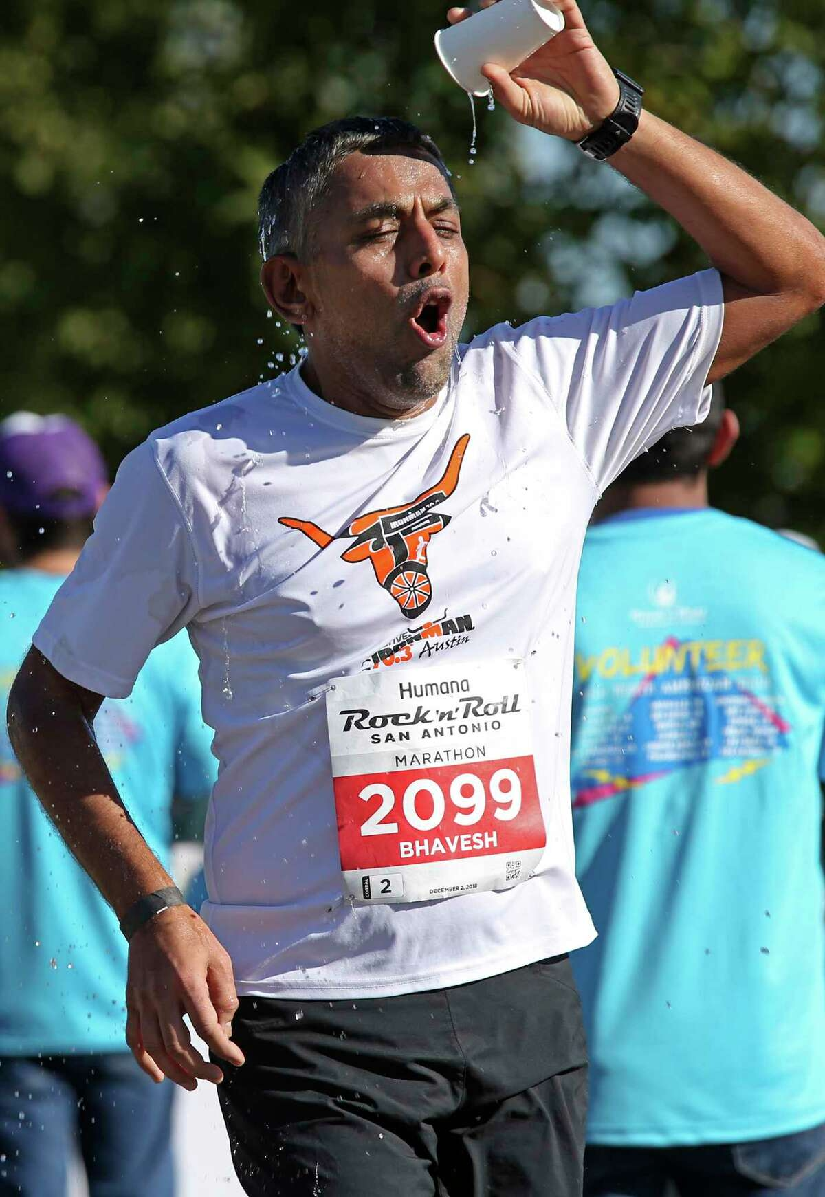Bhavesh Patel, of Lakeway, Texas, refreshes himself at a water station between the 18 and 19 mile marker during the 2018 Humana Rock 'n' Roll San Antonio Marathon and 1/2 Marathon, Sunday, Dec. 2, 2018.