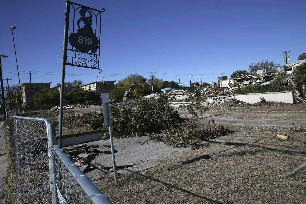 A metal sign still stands during the demolition of The Bright Shawl at 819 Augusta Street on Nov. 26, 2018. The Bright Shawl was opened in in the 1920s as a fundraising project by the Junior League of San Antonio in the 1920s. The land will be used for for a five-story multifamily structure.