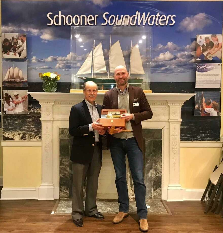 Greenwich resident Scott Mitchell, who is stepping down as chairman of SoundWaters, hands the wheel to the incoming chairman, Doug Bora of Darien. Photo: Contributed /