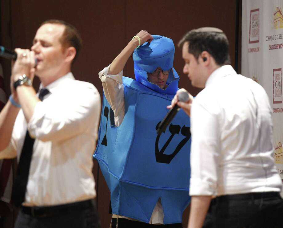 A man dressed as a dreidel spins on stage as the Maccabeats perform a Chanukah Concert at Greenwich Library's Cole Auditorium in Greenwich, Conn. Sunday, Dec. 2, 2018. Presented by Chabad Greenwich, the Jewish a capella group entertained a packed house with a variety of modern pop songs, remixes and Chanukah-themed songs. Photo: Tyler Sizemore / Hearst Connecticut Media / Greenwich Time