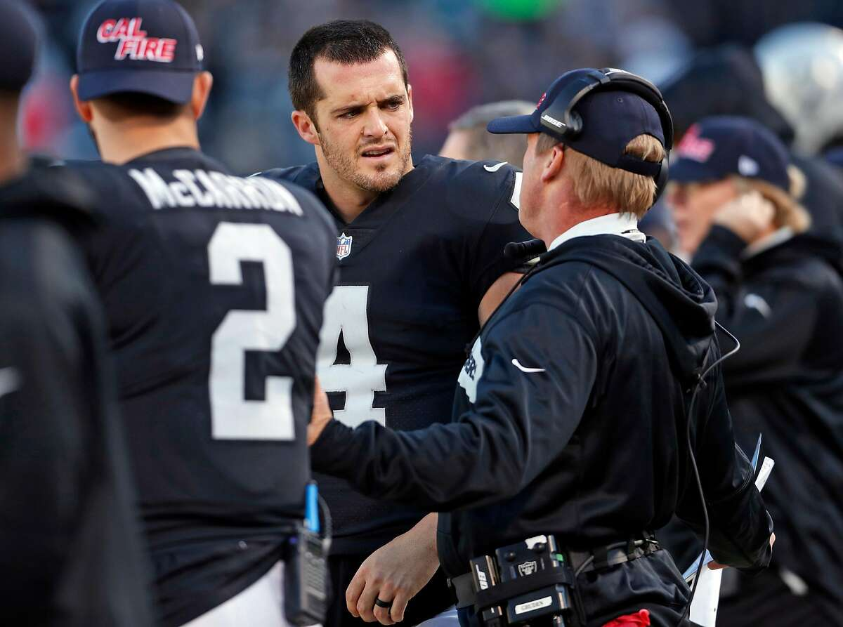 Oakland Raiders' Derek Carr and head coach Jon Gruden have a sideline discussion in 2nd quarter against Kansas City Chiefs during NFL game at Oakland Coliseum in Oakland, Calif. on Sunday, December 2, 2018.