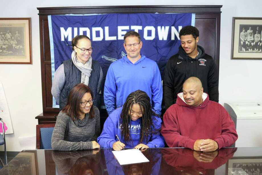 Dominique Highsmith signs her National Letter of Intent with her parents by her side. Also pictured, at top from left: Middletown High AD Elisha De Jesus, softball coach Sal Morello, and Highsmiths brother, Dario. Photo: Paul Augeri / For Hearst Connecticut Media