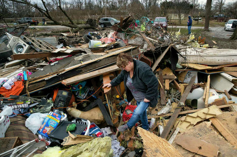 Joyce Morrissey sorts through the debris of her nephew Stephen Tirpak's house in Taylorville, Ill., Sunday, Dec. 2, 2018. The National Weather Service says multiple tornadoes touched down in central Illinois, damaging dozens of structures and injuring multiple people. Photo: Ted Schurter | The State Journal-Register Via AP