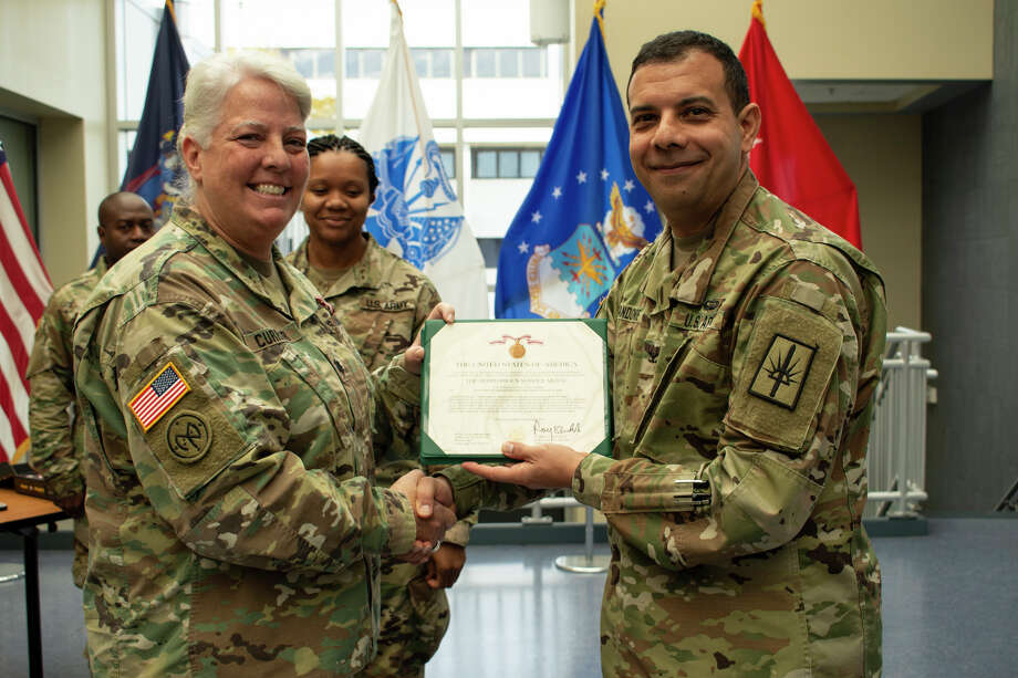 Brig. Gen. John Andonie, New York National Guard chief of staff, presents a Meritorious Service Medal citation to Lt. Col. Lynn Currier during her retirement ceremony at the Joint Force Headquarters in Latham. (New York Army National Guard)