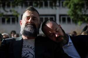 """Bill Arning, left, and his husband Mark McCray, both friends of gay activist Ray Hill, listen during a public memorial service for Hill at City Hall, Sunday, Dec. 2, 2018, in Houston. Hill died Nov. 24, at 78 following a long battle with heart disease. """"Meeting Ray just showed me that this is a city that loves eccentrics,"""" Arning said."""