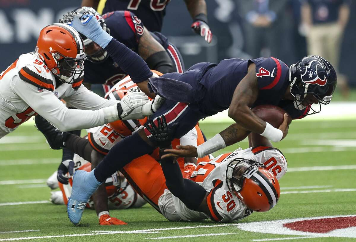 Houston Texans quarterback Deshaun Watson (4) dives over Cleveland Browns defensive end Chris Smith (50) for a first down during the fourth quarter of an NFL football game at NRG Stadium on Sunday, Dec. 2, 2018, in Houston.