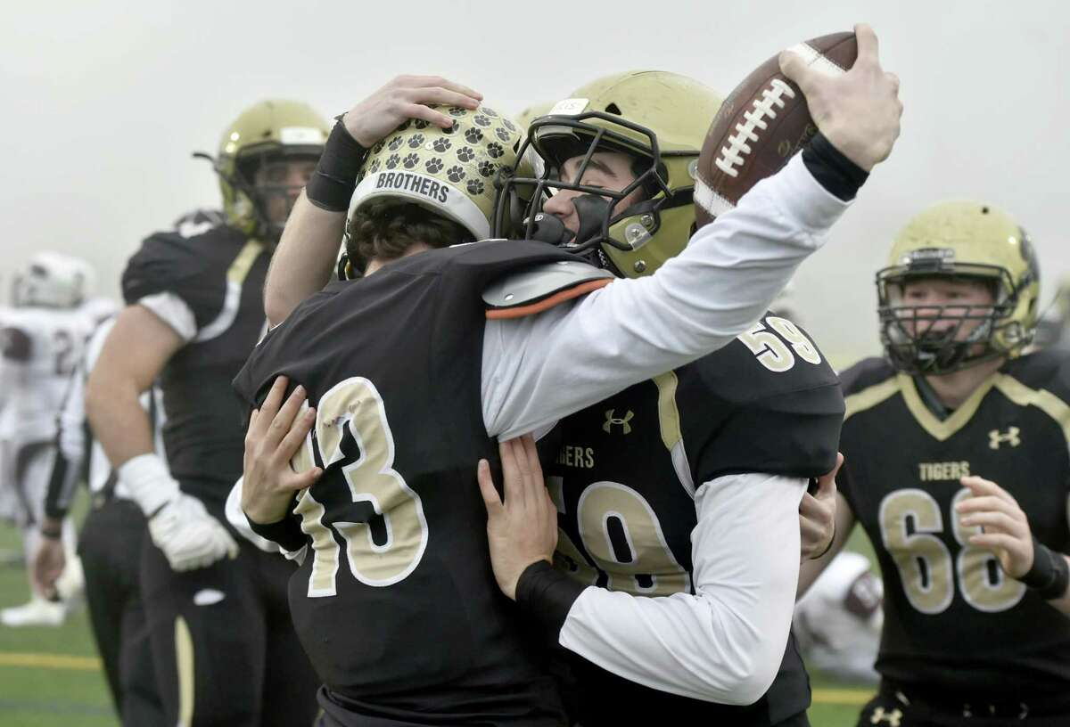 Hand teammates Isaiah McNeilly, left, and Jack Hughes celebrate a score against Windsor on Sunday.