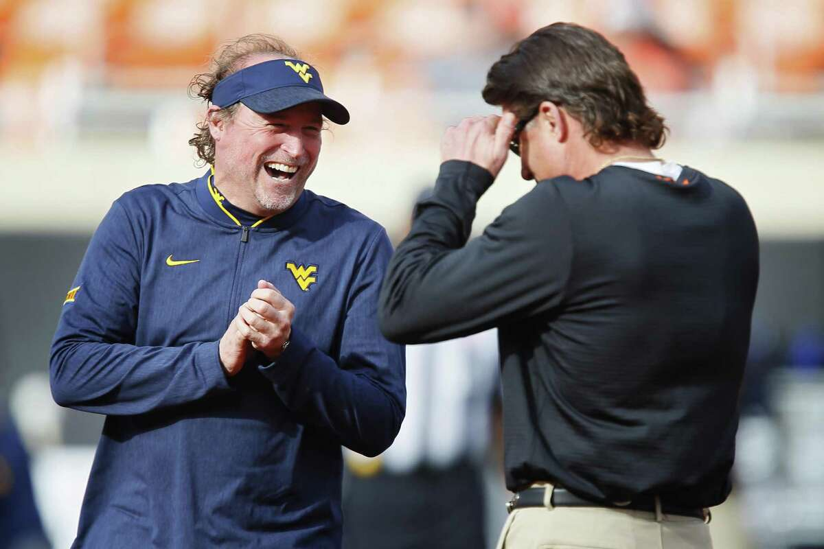 STILLWATER, OK - NOVEMBER 17: Head coach Dana Holgorsen of the West Virginia Mountaineers talks with head coach Mike Gundy of the Oklahoma State Cowboys before their game on November 17, 2018 at Boone Pickens Stadium in Stillwater, Oklahoma. (Photo by Brian Bahr/Getty Images)