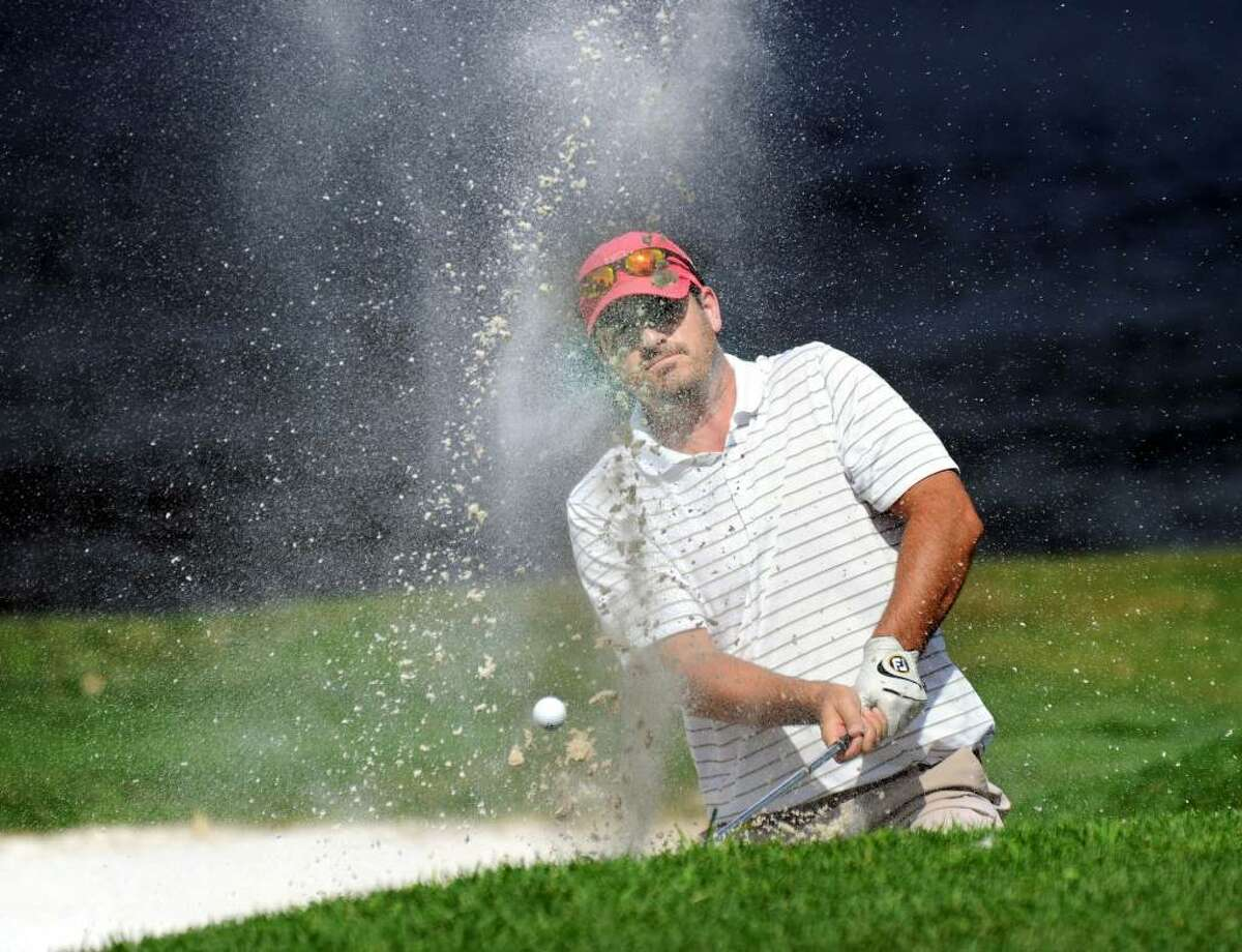 John Belicka, hits a ball out of a sand trap on the 5th hole at Richter Park during the Danbury Amateur Championship Sunday, July 18, 2010.