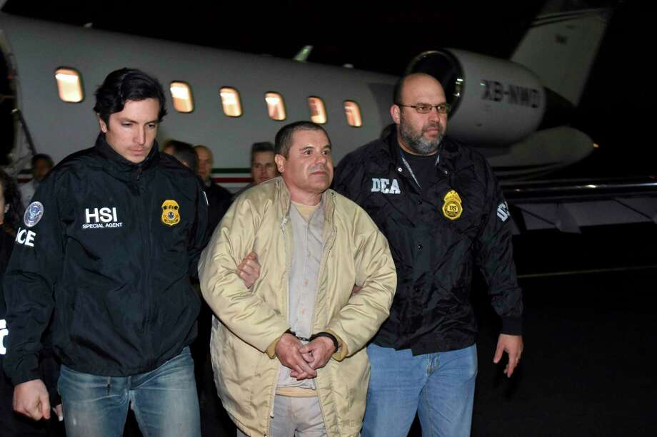 """FILE - In this Jan. 19, 2017, file photo, provided by U.S. law enforcement, authorities escort Joaquin """"El Chapo"""" Guzman, center, from a plane to a waiting caravan of SUVs at Long Island MacArthur Airport, in Ronkonkoma, N.Y. On Monday, Nov. 26, 2018, a government witness testifying at the U.S. trial of the Mexican drug lord known as """"El Chapo"""" claims his cartel paid massive bribes to a top law enforcement official. (U.S. Law Enforcement via AP, File) / U.S. Law Enforcement"""
