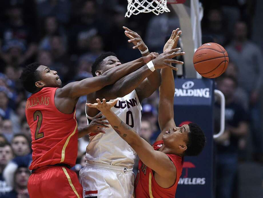 Arizona's Brandon Williams (2) blocks a shot attempt by UConn's Eric Cobb (0) as Arizona's Ira Lee (11) defends during the first half Sunday. Photo: Jessica Hill / Associated Press / Copyright 2018 The Associated Press. All rights reserved