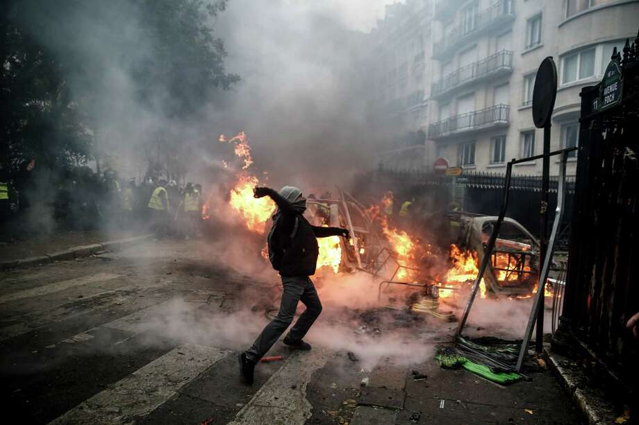 TOPSHOT - A protester throws projectile at riot police during a protest of Yellow vests (Gilets jaunes) against rising oil prices and living costs, on December 1, 2018 in Paris. (Photo by Abdulmonam EASSA / AFP)ABDULMONAM EASSA/AFP/Getty Images Photo: ABDULMONAM EASSA / AFP or licensors