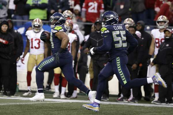 Seattle Seahawks middle linebacker Bobby Wagner, left, runs with defensive end Frank Clark (55) after intercepting a pass and running for a 98-yard touchdown against the San Francisco 49ers during the second half of an NFL football game, Sunday, Dec. 2, 2018, in Seattle. (AP Photo/Elaine Thompson)