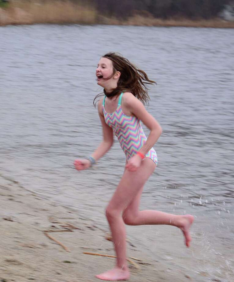 Penny Morrissey, 10, from New Milford runs out of the water after the plunge during Washington Montessori School's seventh annual Polar Plunge fundraiser on Sunday at Lake Waramaug State Park in New Preston. The school's program provides middle school education to six graduates from the Children's Community School in Waterbury each year. It has been in place since 2005. Photo: Lisa Weir / For Hearst Connecticut Media / The News-Times Freelance