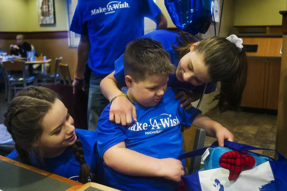 Cutler Doud, 7, center, opens a gift from the staff at Culver's alongside two of his sisters, Tirzah, 16, left, and Thea, 14, right, during a going-away party Sunday, Dec. 2, 2018 for the Doud family's upcoming Disney cruise arranged by Make-A-Wish. (Katy Kildee/kkildee@mdn.net) Photo: (Katy Kildee/kkildee@mdn.net)