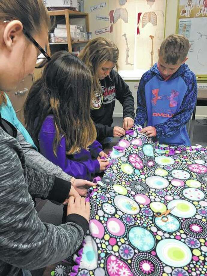 Salem Lutheran School fifth- through seventh-graders tie fleece blankets that later were donated to New Directions Warming and Cooling Center. Photo: Photo Provided