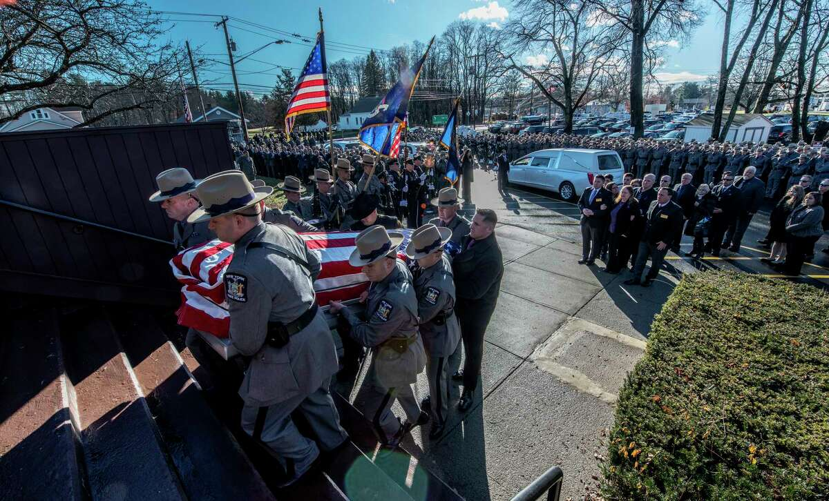 The casket is carried in to St. Gabriel The Archangel Roman Catholic Church for the funeral of Trooper Jeremy VanNostrand as family follows Monday Dec. 3, 2018 in Schenectady, N.Y. (Skip Dickstein/Times Union)