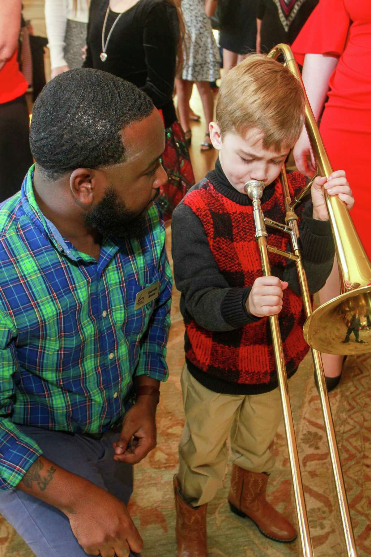 Garrett Shaw of the Houston Symphony introduces the trombone to William Keeton, 5, at Houston Symphony's Magical Musical Morning.