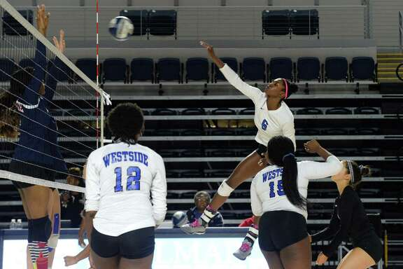 Westside's Kylah Carter spikes as teammates Mallori Sims (15) and Caytlin Willis (12) look on during a high school volleyball match between the Westside Wolves and the Carnegie Vanguard Rhinos on October 20, 2018 at Delmar Fieldhouse, Houston, TX.