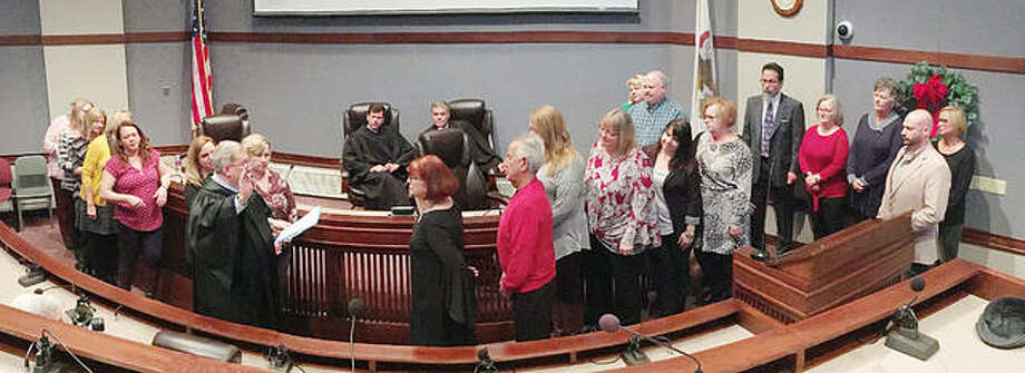 County Clerk Debra Ming-Mendoza, with her husband, Mercie, and her clerk's office staff in support, is sworn in Monday morning by Circuit Judge Dennis Ruth during a swearing-in ceremony at the Madison County Administration Building. Photo: For The Telegraph