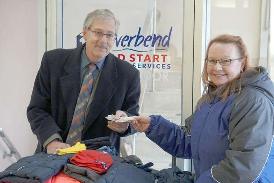 Tim Hinrichs of Alton-Godfrey Rotary delivers coats and cash to Judy Gann for the Riverbend Head Start & Family Services' annual Coats for Kids drive. Photo: For The Telegraph