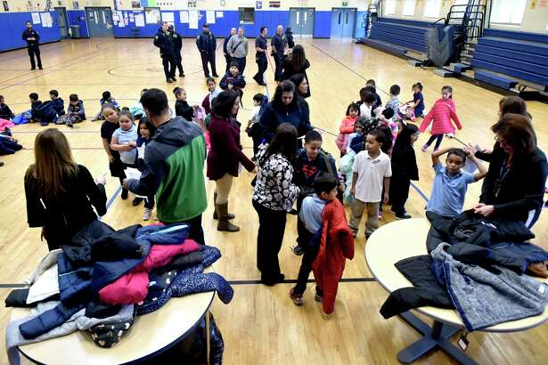 New Haven, Connecticut - Monday, December 3, 2018: 300 winter coats are given out to children in need Monday morning at the Clinton Avenue School in New Haven. The coat drive and giveaway event at the school, in its second year, is sponsored by the Servpro of Meriden and the Connecticut Shoreline and organized by Leshea Schaivone (CQ) of Hamden to honor the memory of her mother Donna Schaivone.