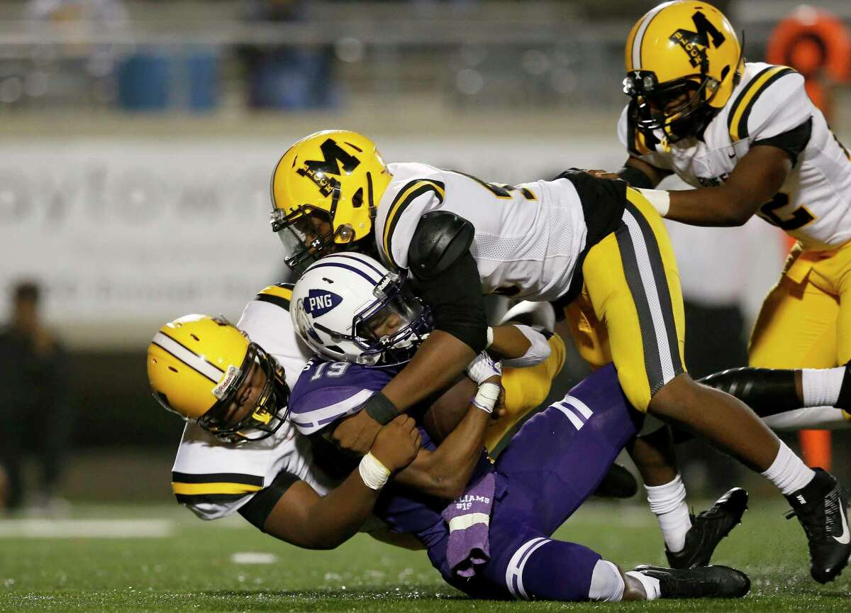 Port Neches-Groves Indians running back Jaylan Williams (19) is tackled by Fort Bend Marshall Buffalos defensive end Warren Robinson (45) and Fort Bend Marshall Buffalos defensive tackle Detreveyon Thomas (97) during the high school football playoff game between the Port Neches-Groves Indians and the Fort Bend Marshall Buffalos in Baytown, TX on Friday, November 30, 2018.