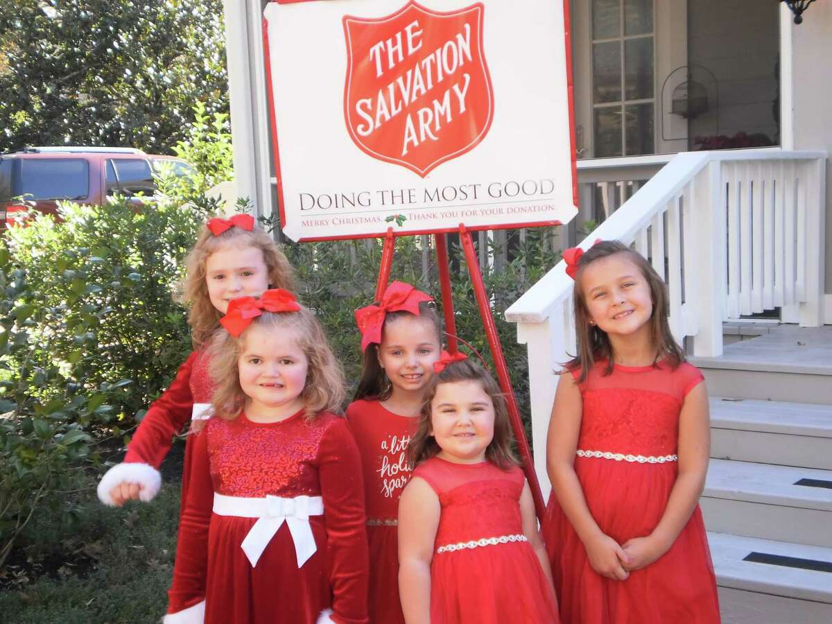 A group of young ladies poses for a picture with the Salvation Army kettle prior to attending the 32nd Salvation Army Doll and Bear Tea in Conroe Sunday afternoon. This year's event is set for Sunday, Dec. 8, at the home of Carol and Howard Crockett.