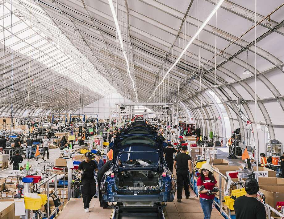 Workers assemble Model 3s in a tent at Tesla's factory in Fremont. African American workers have reported threats, humiliation and barriers to promotion at the plant. The automaker says there is no pattern of bias. Photo: Justin Kaneps / New York Times