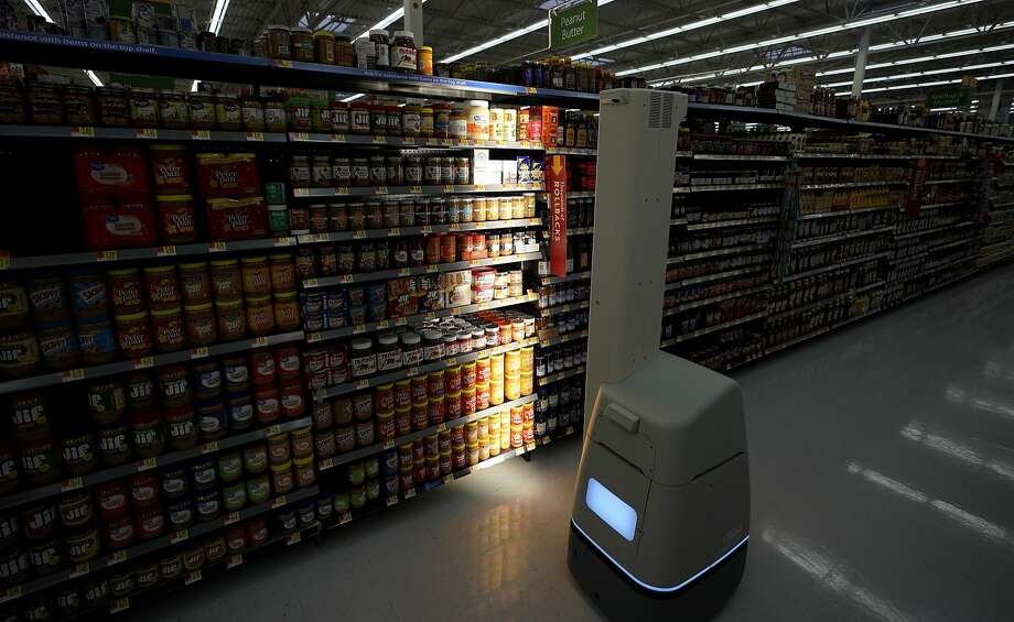A robot scans shelves to provide inventory data at a Walmart Supercenter in Houston. The next automated task for robots will be scrubbing floors of stores starting next month, Walmart says. Photo: David J. Phillip / Associated Press