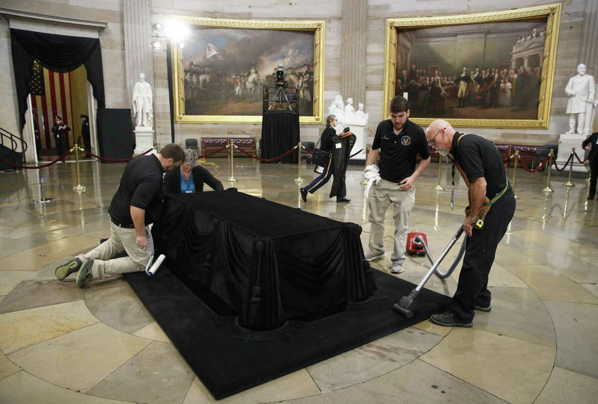 Mike Dean, right, lead upholsterer for the House of Representatives, and John Brady Jr., second from right, an apprentice, prepare the Lincoln Catafalque for the casket of former President George H.W. Bush, who died Friday at age 94, in the Capitol Rotunda in Washington, Monday, Dec. 3, 2018. (AP Photo/Patrick Semansky)