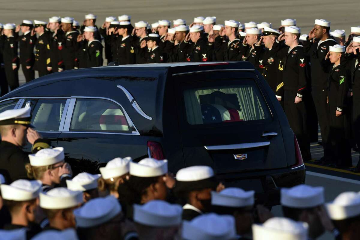 Sailors from the USS George HW Bush, the newsiest aircraft carrier in the fleet, pay their respects as the flag-draped casket of former President George H.W. Bush passes by at Andrews Air Force Base in Md., Monday, Dec. 3, 2018. (AP Photo/Susan Walsh)