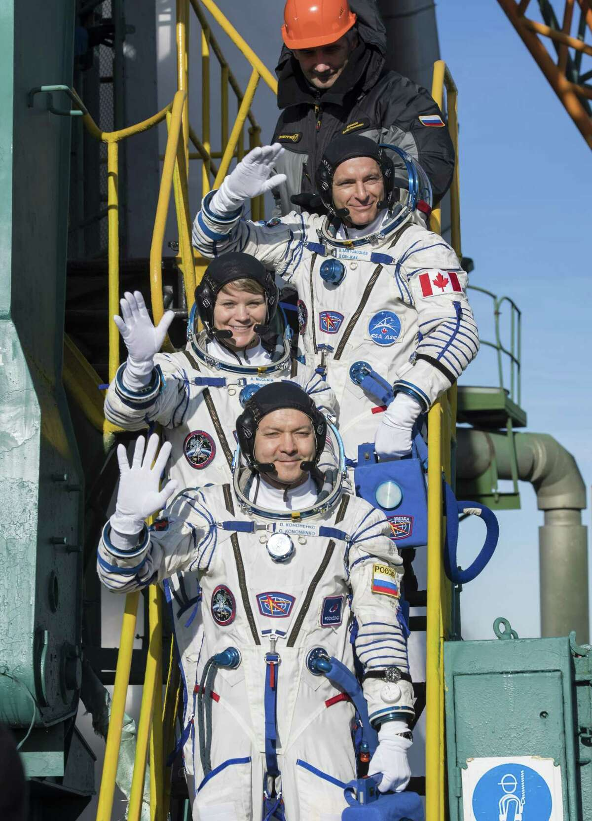 In this handout provided by NASA, Expedition 58 Flight Engineer David Saint-Jacques of the Canadian Space Agency (CSA), (top), Flight Engineer Anne McClain of NASA (C) and Soyuz Commander Oleg Kononenko of Roscosmos, (bottom), wave farewell prior to boarding the Soyuz MS-11 spacecraft for launch at the Baikonur Cosmodrome on December 3, 2018 in Baikonur, Kazakhstan. Launch of the Soyuz rocket is scheduled for December 3 and will carry Expedition 58 Soyuz Commander Oleg Kononenko of Roscosmos, Flight Engineer Anne McClain of NASA, and Flight Engineer David Saint-Jacques of the Canadian Space Agency (CSA) into orbit to begin their six and a half month mission on the International Space Station.
