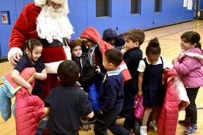 New Haven, Connecticut - Monday, December 3, 2018: Santa Claus visits with children after 300 winter coats were given out to children in need Monday morning at the Clinton Avenue School in New Haven The coat drive and giveaway event at the school, in its second year, is sponsored by the Servpro of Meriden and the Connecticut Shoreline and organized by Leshea Schaivone (CQ) of Hamden to honor the memory of her mother Donna Schaivone.
