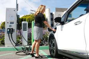 Esther M. de Frutos, an Uber driver of one year, prepares to charge her Chevy Bolt EV electric car at a Walgreens on Monday, June 18, 2018 in San Francisco, Calif.
