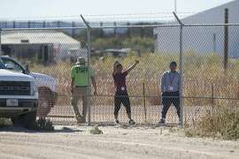In this Nov. 15, 2018 photo provided by Ivan Pierre Aguirre, migrant teens held inside the Tornillo detention camp smile at protestors waving at them outside the fences surrounding the facility in Tornillo, Texas. The Trump administration announced in June 2018 that it would open the temporary shelter for up to 360 migrant children in this isolated corner of the Texas desert. Less than six months later, the facility has expanded into a detention camp holding thousands of teenagers - and it shows every sign of becoming more permanent. (Ivan Pierre Aguirre via AP)