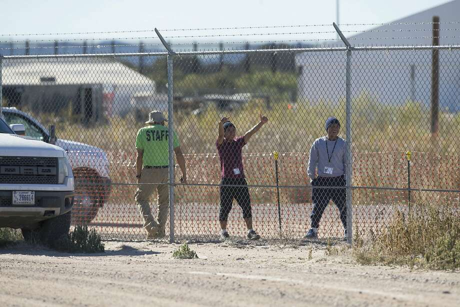 Migrant teens held inside a Tornillo, Texas, detention camp for undocumented immigrants smile at protesters waving at them outside the fences surrounding the facility on Nov. 15. Photo: Ivan Pierre Aguirre / Associated Press