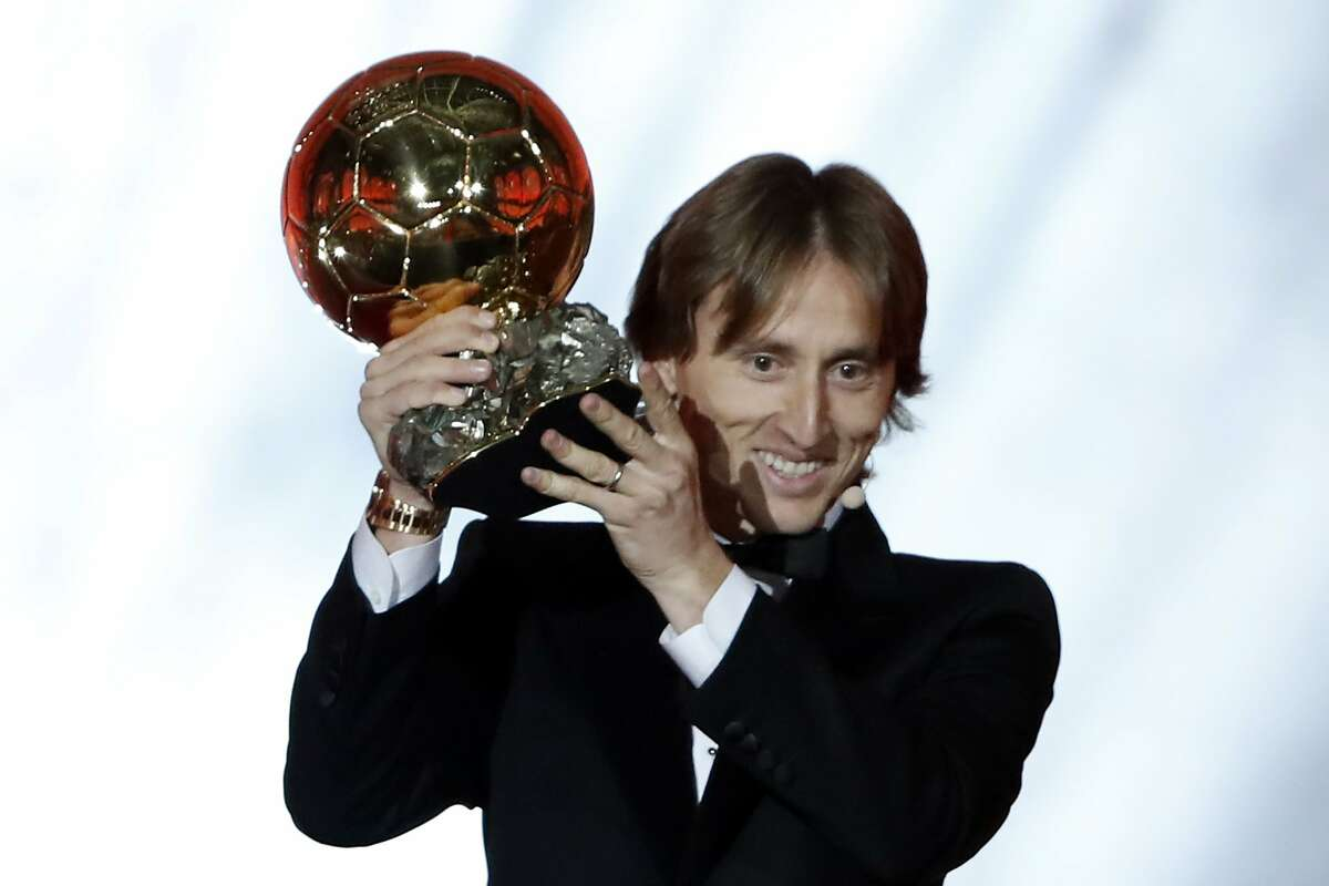 Real Madrid's Luka Modric celebrates with the Ballon d'Or award during the Golden Ball award ceremony at the Grand Palais in Paris, France, Monday, Dec. 3, 2018. Awarded every year by France Football magazine since Stanley Matthews won it in 1956, the Ballon d'Or, Golden Ball for the best player of the year will be given to both a woman and a man. (AP Photo/Christophe Ena)